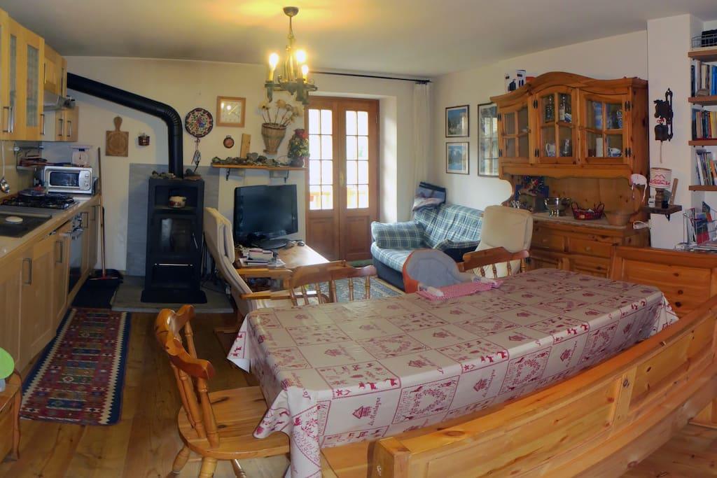 sala con cucina, tv, computer, tavolo , stufa a legna