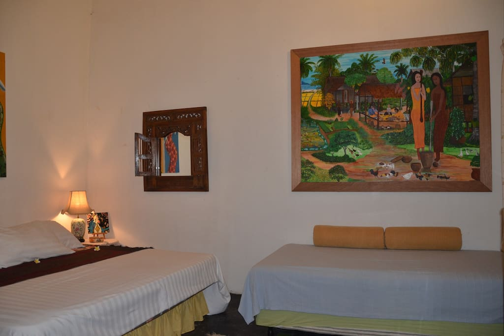 Painting of Langkawi village life over the super-single bed.