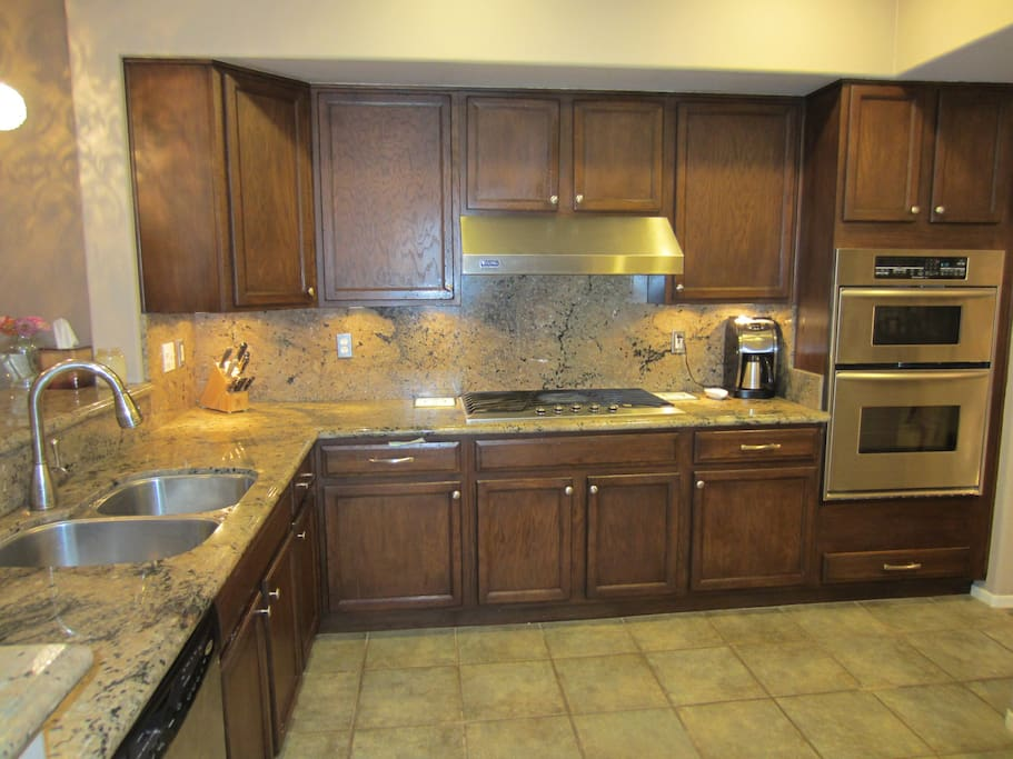 Beautiful cabinetry, slab granite countertops, under lighting, and double sided deep sink