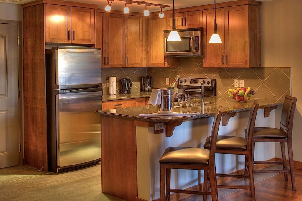 This sleek kitchen has stainless steel appliances and a breakfast bar.