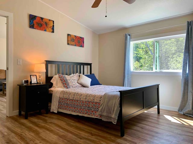 Master Bedroom - queen size bed with quilt and extra blanket, nightstand, and alarm clock.