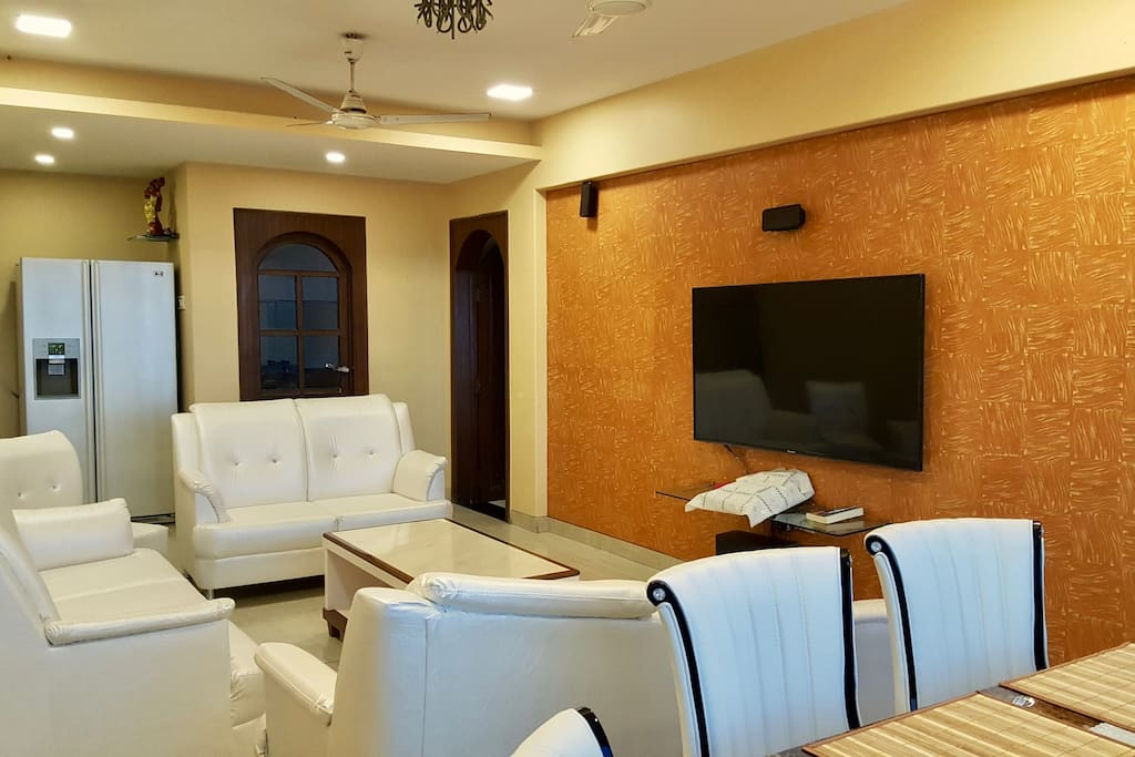 Living Room with plush comfy furniture and fantastic Home Theatre system and smart refrigerator.