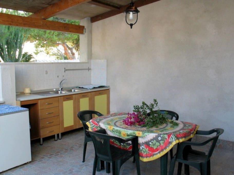 La cucina nella veranda coperta da una tettoia il legno.