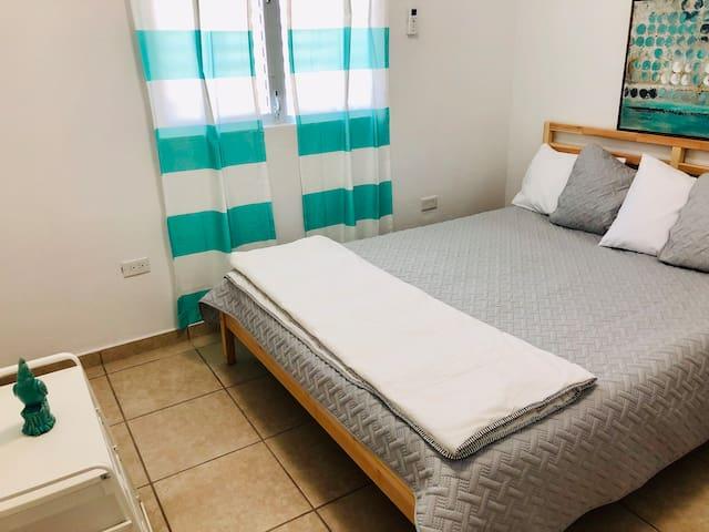 Queen bed and dresser inside bedroom.