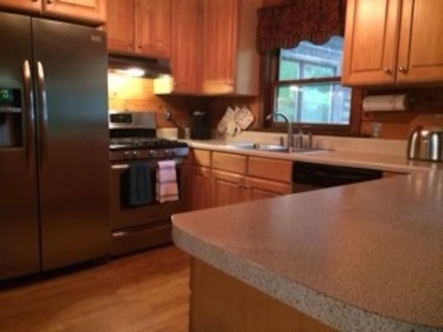 Kitchen with updated appliances and gas range.