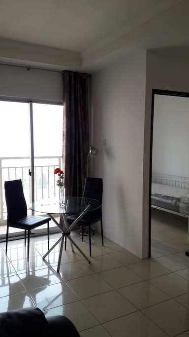 Dining table by the balcony. Bedroom2: Single bed.