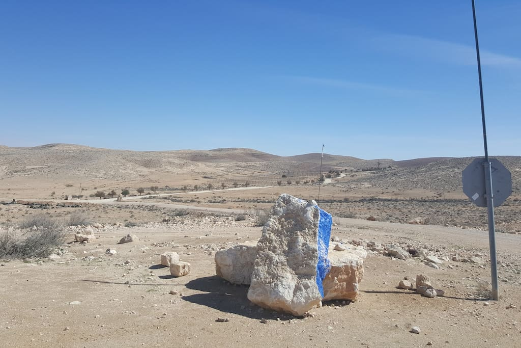 The rock painted blue indicating the entrance of the farm.