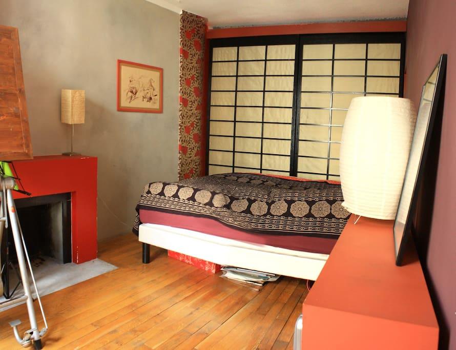 Une chambre pour deux personnes, avec parquet, cheminée et rangements.