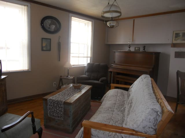 Living room space with piano used by hosts only when guests are staying in the farmhouse.