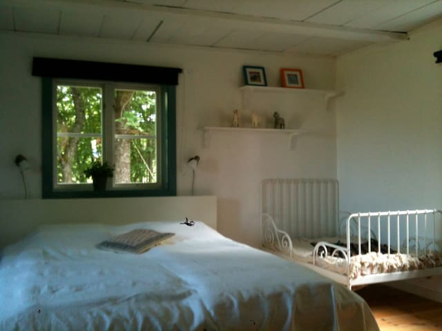 Det stora sovrummet är svalt och skönt med vackra bjälkar och öppen spis. Barnsängen går att dra ut till full storlek