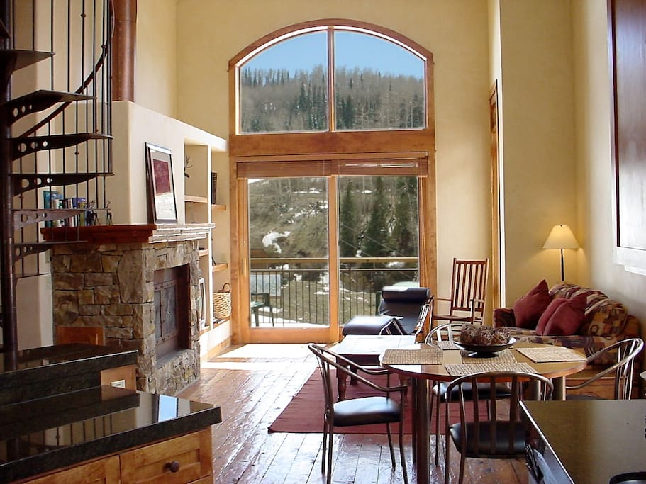 It's easy to relax in the living room with its fireplace, big windows, and high ceilings.
