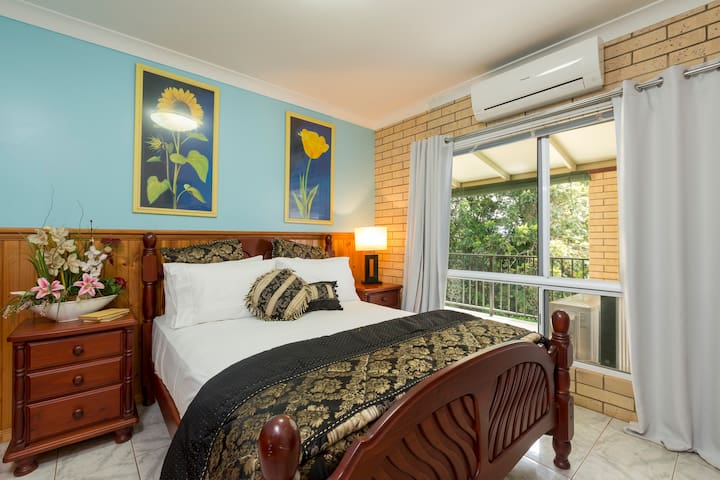 Second bedroom (main house) - comfy queen bed and large window overlooking rainforest