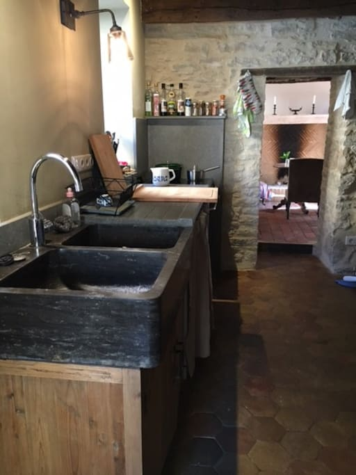 La cuisine tout confort avec plan de travail en pierre des carrière de Montagny, évier en pierre.