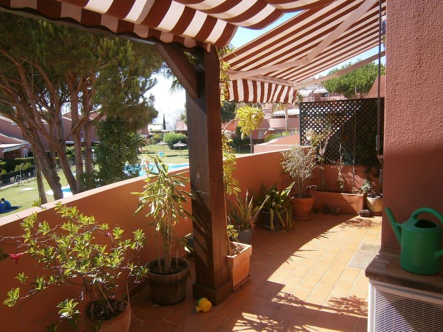 terraza con mesa y sillas y toldos, con vistas a la piscina y jardines