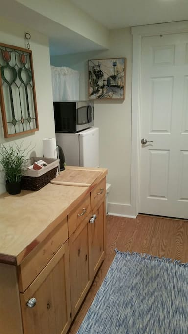 Kitchenette with fridge, microwave, kettle, and dishes.
