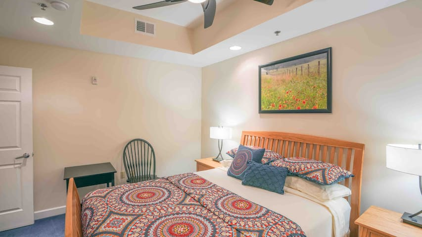 Second bedroom boasts a queen bed, sitting area and a wardrobe with a TV.