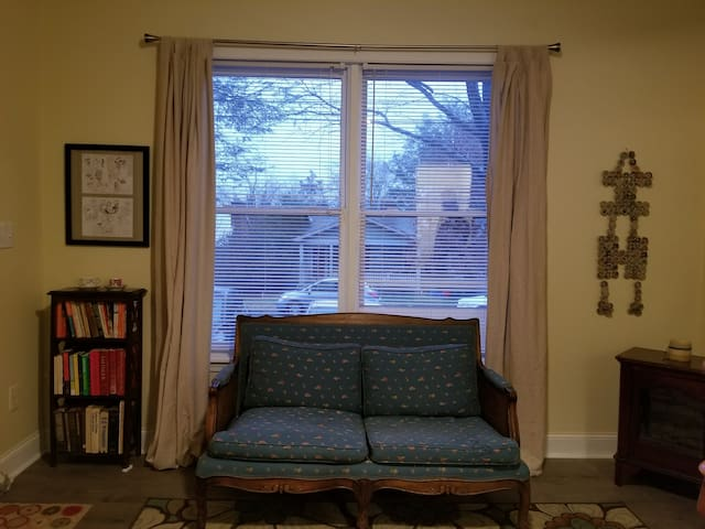 Sweet love seat and books for your reading pleasure. View to street in front.