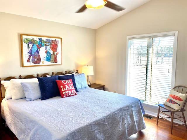This guest bedroom has a king size bed for your comfort. Original artwork hangs on the walls. There are gorgeous views of the lake from this bedroom. There is a full bathroom down the hall.