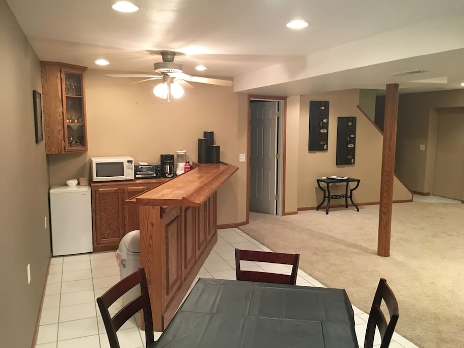 Bar area with dining table, fridge, microwave, toaster oven, coffee maker, and blender.