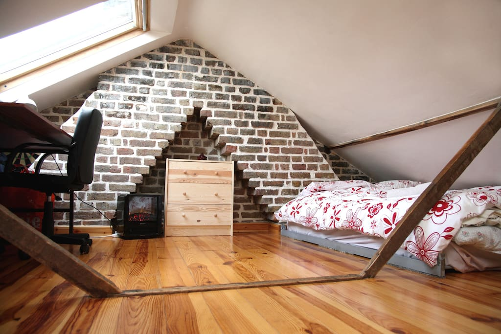 Loft with double bed and chest of drawers and desk with comfortable chair.