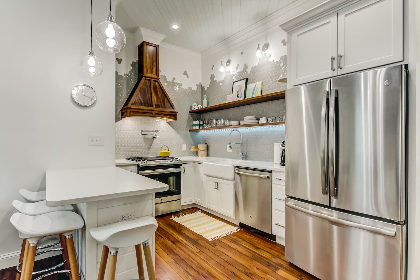 Bright and modern kitchen is equipped with high end appliances, farmhouse sink, gas stove, all the essentials, and then some!