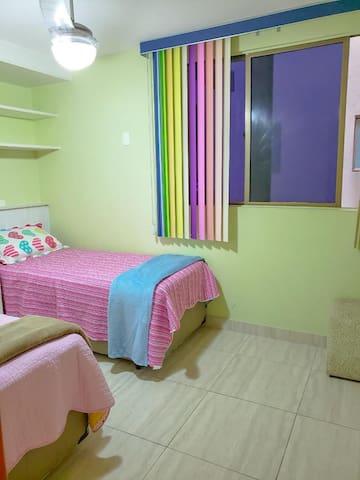 2 camas de solteiro e espaço para colchonete no chão.