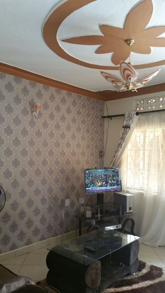 sitting room refurbished with  wall papered  including flat screen t.v centre table carpet in centre sofas home cinema music  system fan dvd player etc