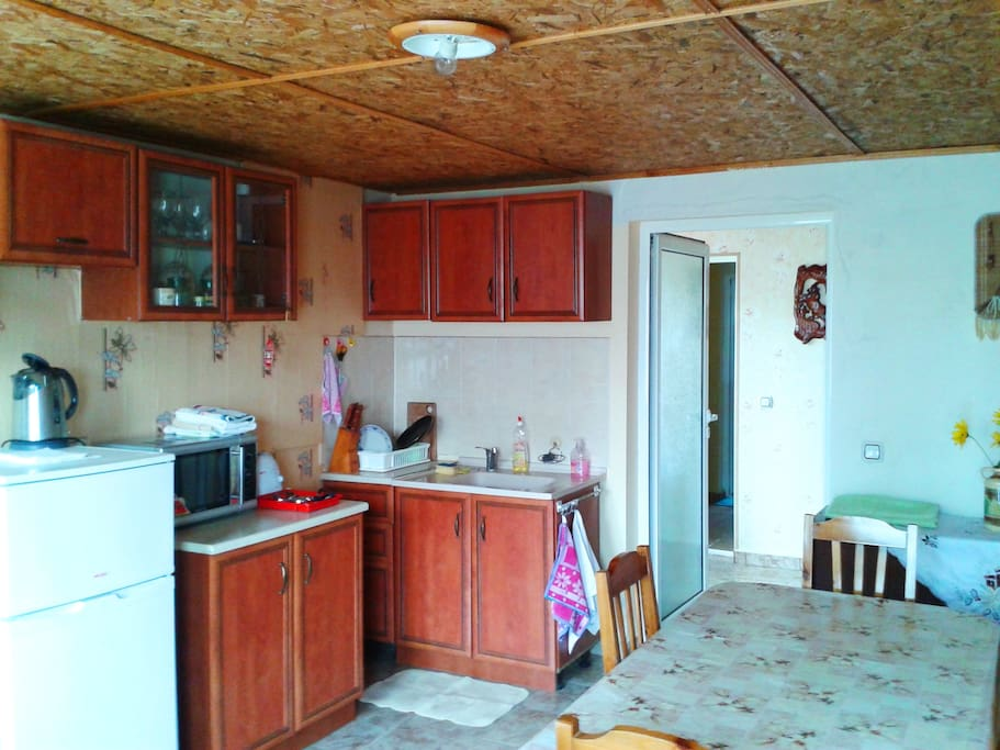 Kitchen, with a microwave oven, refrigerator with a freezer camera, sink, table for 7-8 persons