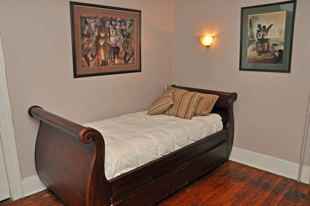 pottery barn twin sleigh bed that is extra long with a comfortable mattress; a second bed is hidden underneath this bed in the form of a trundle