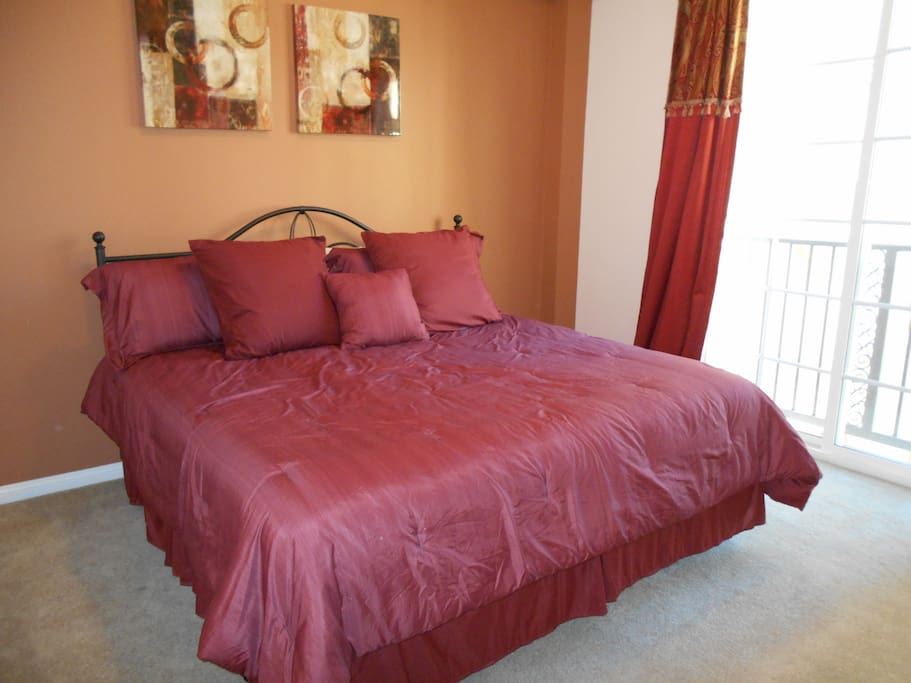 Master bedroom features king size bed and patio doors with Juliet balcony overlooking courtyard.