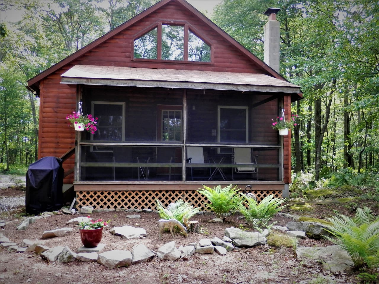 View of back of cabin with screened porch for relaxing.