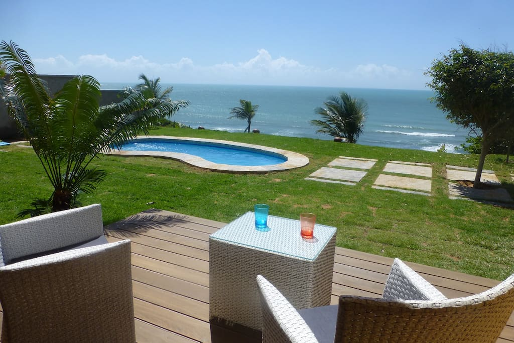 Outlook from bedroom with garden, swimming pool and ocean