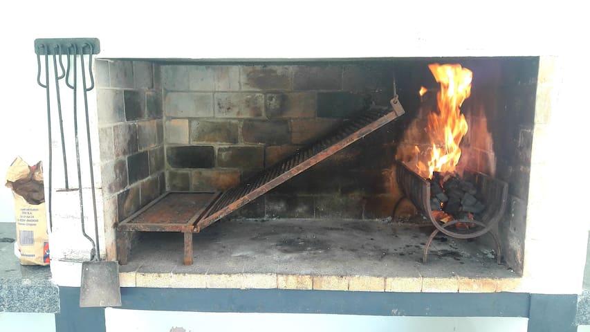 El sector parrillas cuenta con todo lo necesario para el asado, mesas y sillas.