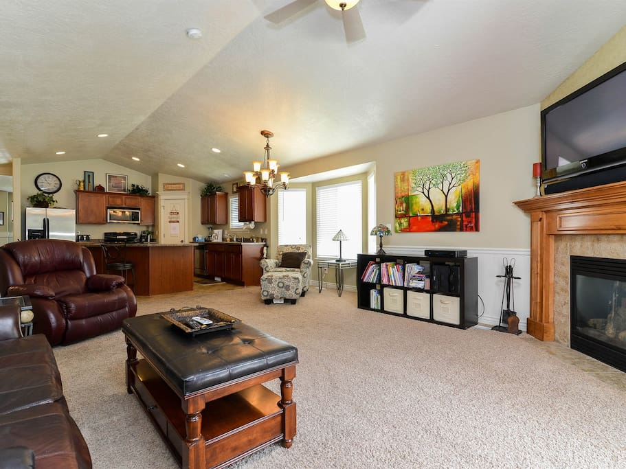 Spacious open concept family room adjacent to kitchen with gas fireplace, leather sofa and recliner and vaulted ceiling
