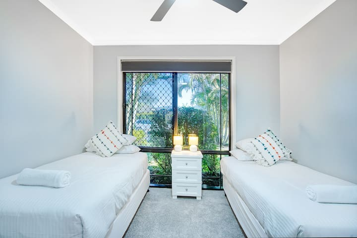 A third bedroom sleeps two in separate single beds with carpeted flooring and a ceiling fan.