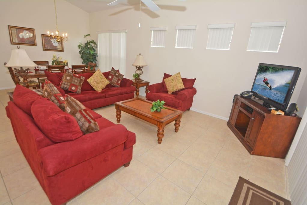 Family seating area with comfortable sofas, large flatscreen TV and patio doors to the pool area