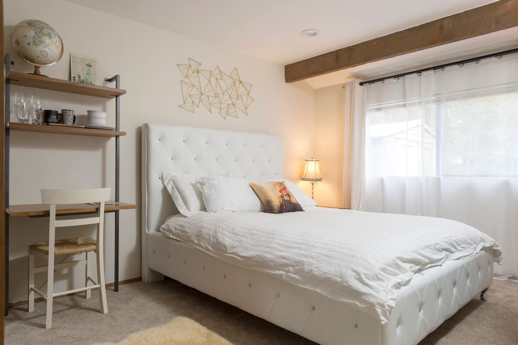 First bedroom - queen bed, desk, chair, mini fridge, Keurig coffee machine, microwave, cutlery, bowls, plates, luggage rack, full length mirror, hangers, digital alarm clock, blackout curtains and soft guest bathrobes