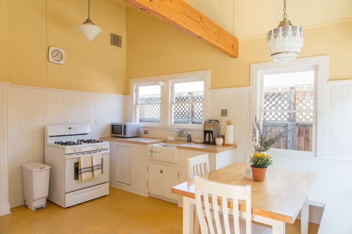 Amazing kitchen to cook or hang out in. High, pitched yellow tin ceiling with two ceiling fans.