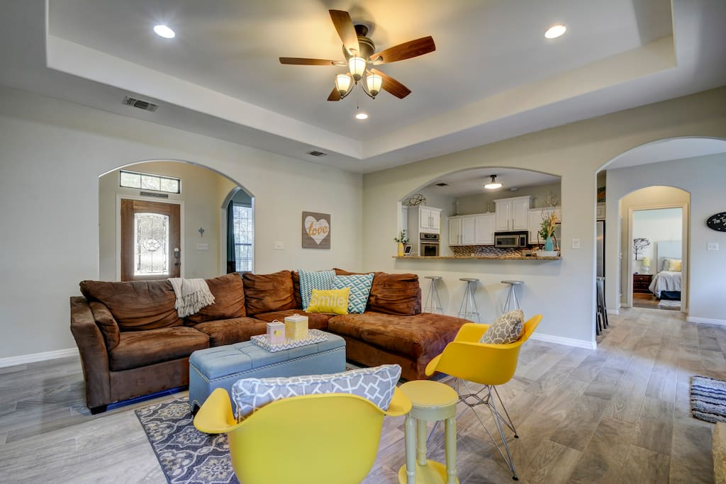 Gather together in the large living room with cozy sectional and fun pops of color in the yellow arm chairs