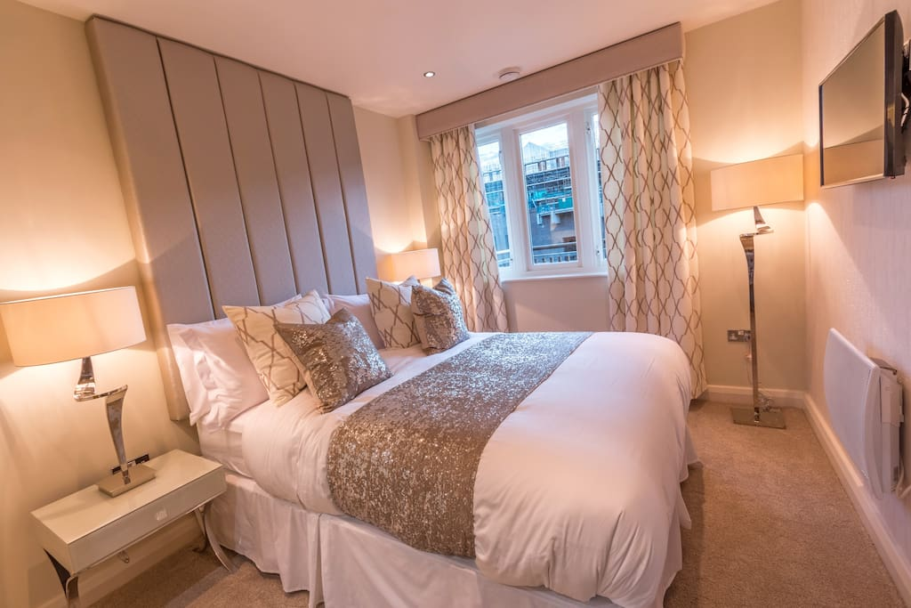 Riverside master bedroom with comfy King Size Bed, crisp white bedding, luxury furnishings, widescreen tv with Netflix and bespoke fittings including fitted robes with lit dressing area.
