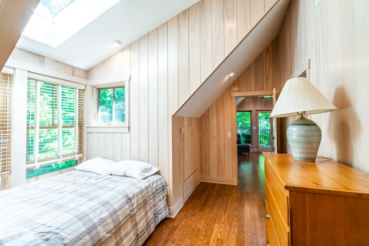 Hallway bed nook with double bed.  Doorway at the end leads to the master bedroom