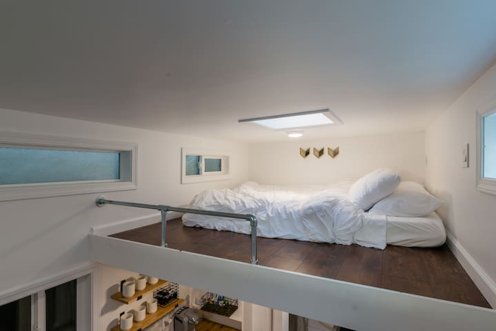 """Sleeping loft with skylight.  Height is 3'5"""" and has a safety rail.  Comfy queen size bed with 4 pillows"""