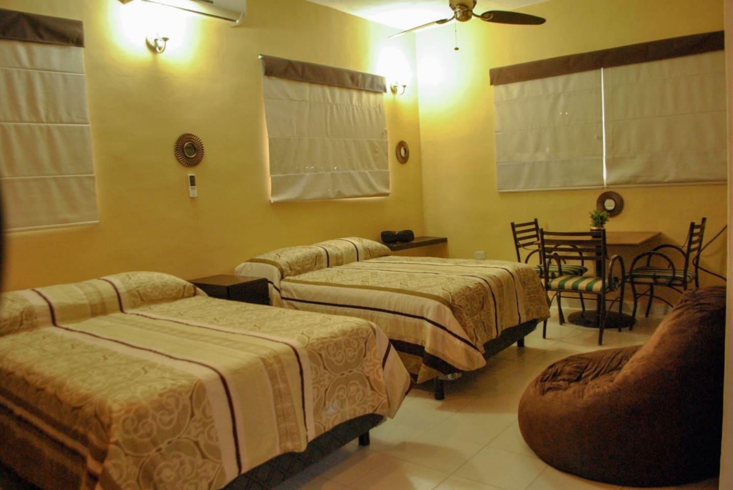 Dos camas matrimoniales, mesa, A/A, baño amplio privado, closet amplio y tocador para maquillaje con espejo.