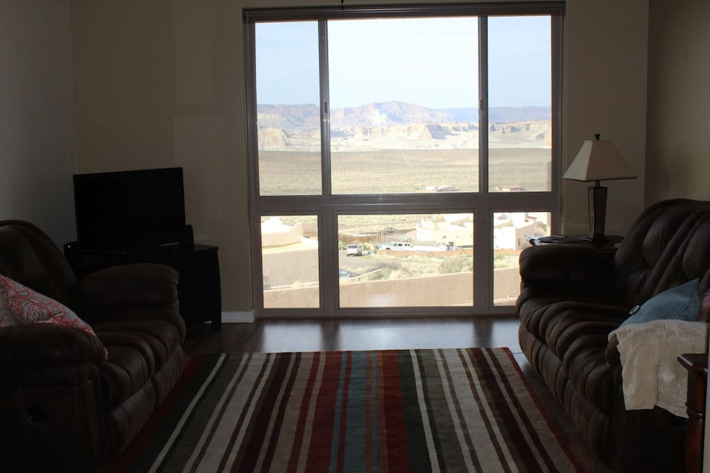 picture window in living room with views of buttes and lake