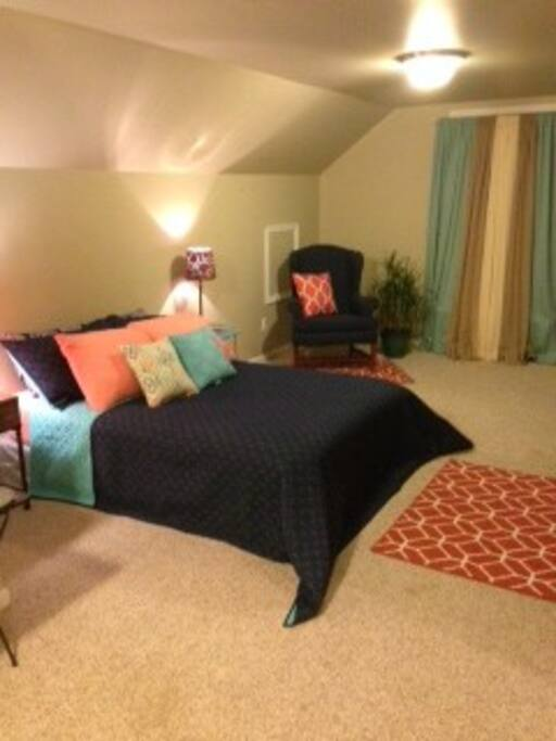 Full size bed with new bedding and seating area