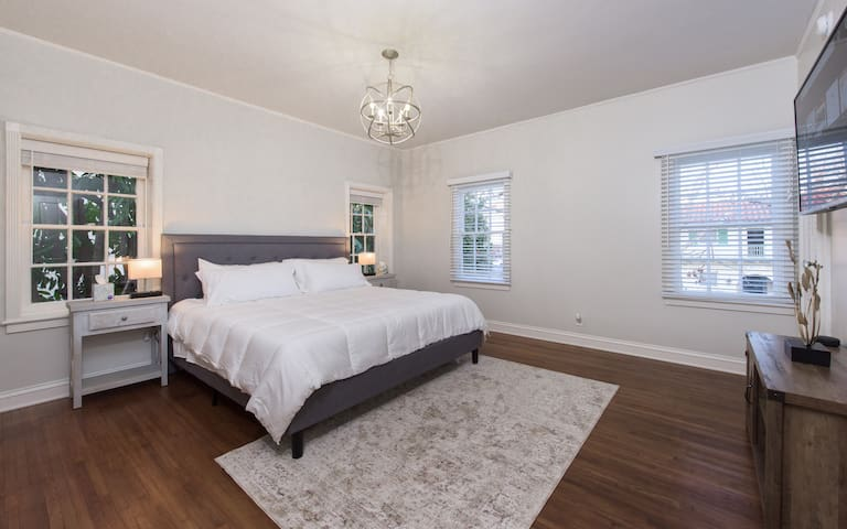 """Master Bedroom with King Size Bed and hardwood floors throughout. Large windows overlooking a sycamore-lined street and lush greenery. 55"""" LG Smart TV w Netflix & Amazon Prime. Smart bedside lighting."""