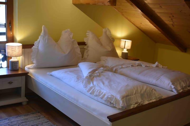 Das große Schlafzimmer mit der Dachschräge und viel Holz ...