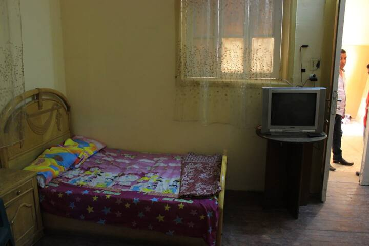 A Single Bed at Men only Dormitory Shared Bathroom