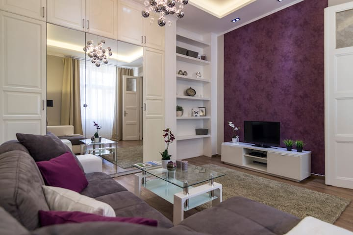 Spacious and bright living room with comfortable couch and LED tv
