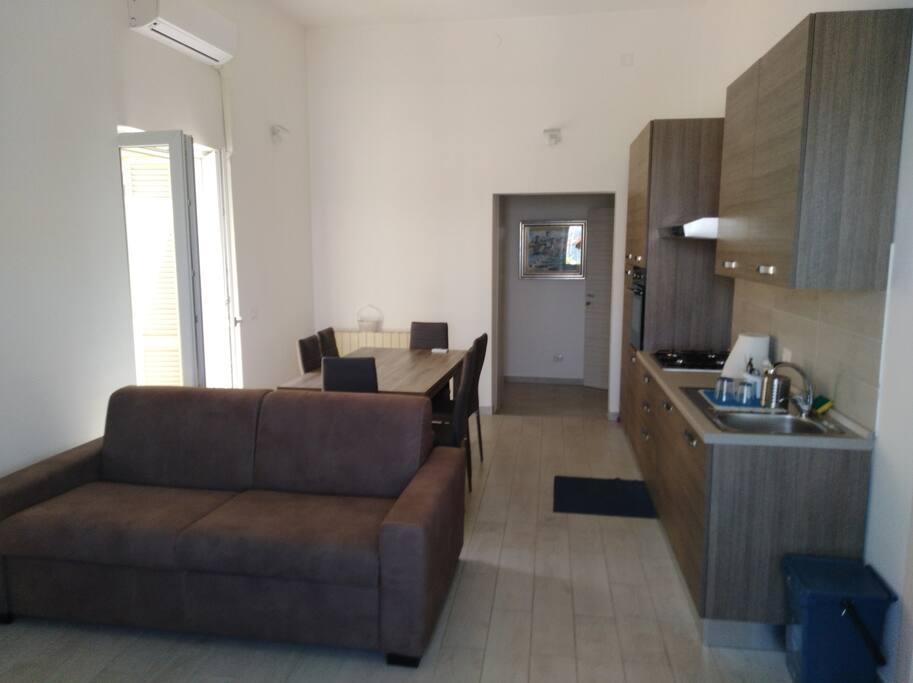 Entrata lounge con divano letto matrimoniale e cucina fornita di tutto.